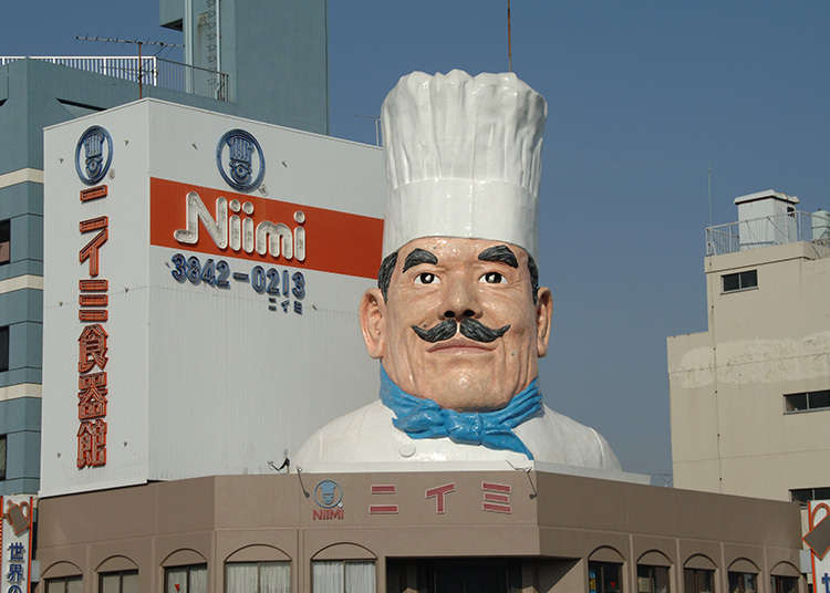 A restaurant supply store with a giant statue of a cook as its landmark
