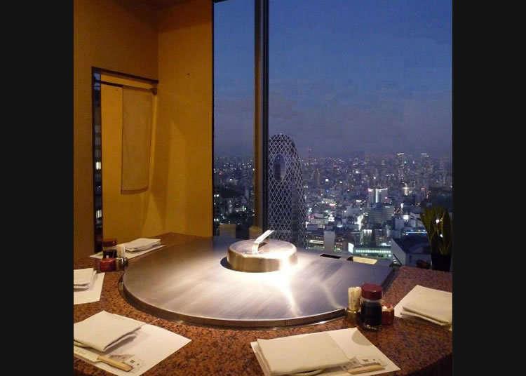Pemandangan malam yang terhampar di seluruh bagian jendela dan hidangan lezat teppan yaki.